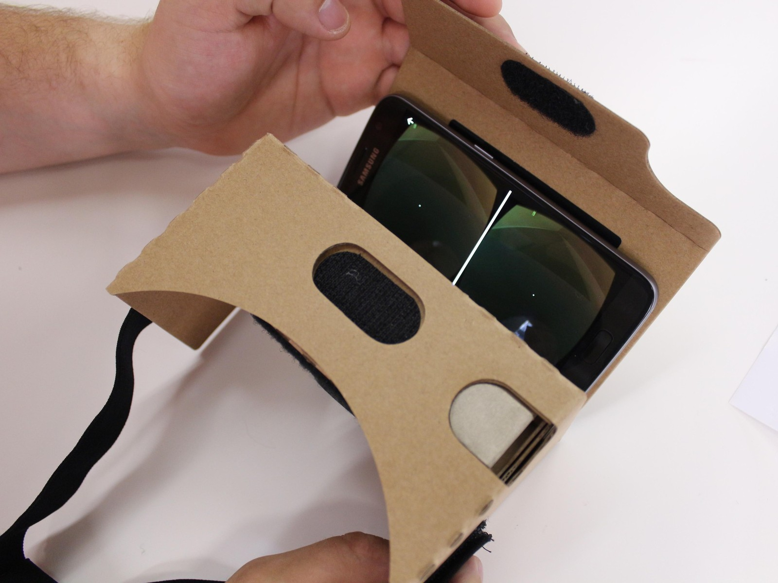 Place your phone in the Cardboard phone holder and you should see the VR display pop up. Seal up the velcro at the top and you're good to go!